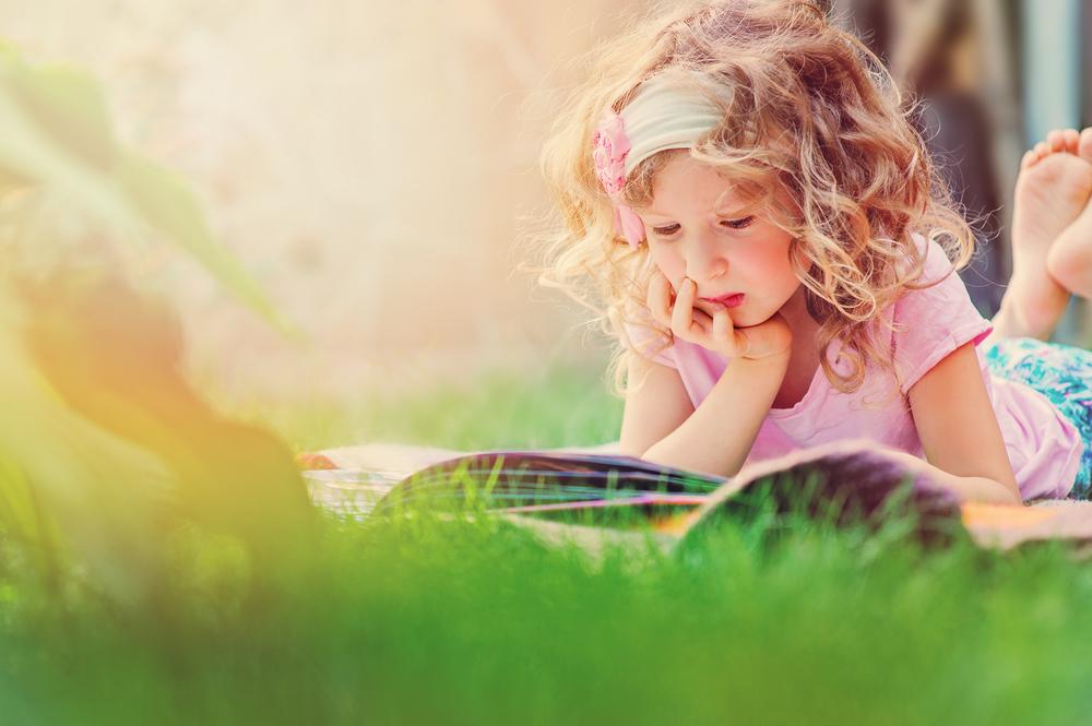 Holčička čte knihu v trávě