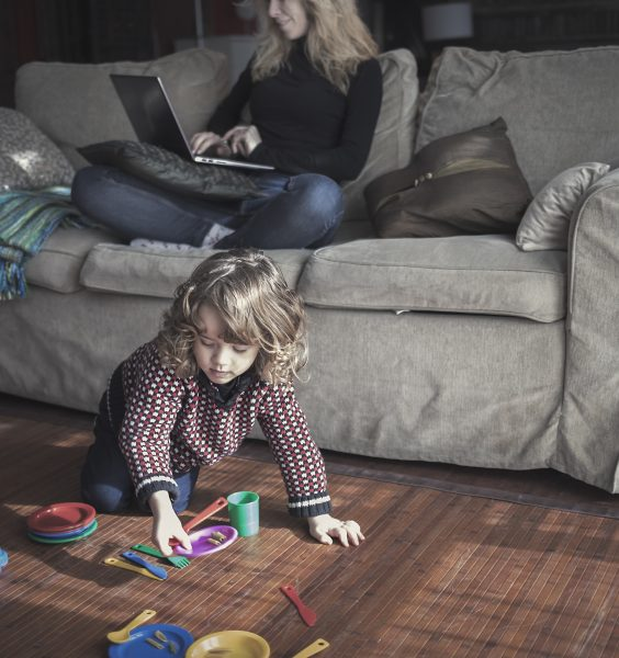 Matka pracuje na gauči a dítě si hraje