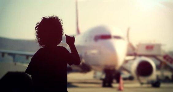 Dítě v letištní hale sleduje letadlo