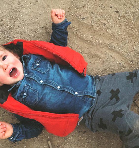 Dítě na písku ležící na zádech