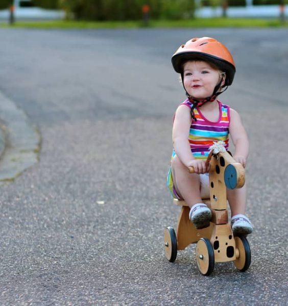 Holčička s bezpečností helmou na tříkolce