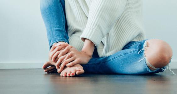 Žena sedící na podlaze mimoděložní těhotenství