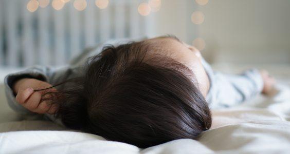 Dítě ležící na zádech v posteli