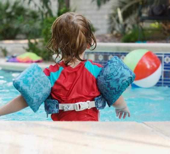 Dítě s nafukovacími křidélky v bazénu