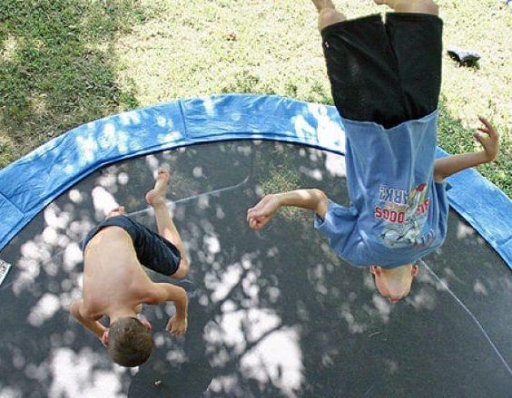 Děti skáčou kotrmelce na trampolíně