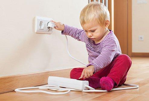 Dítě si hraje s elektrickou zásuvkou