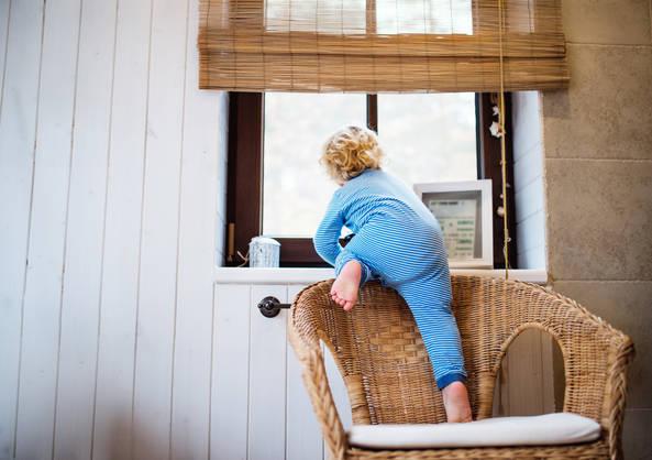 Dítě leze na kraj gauče k oknu