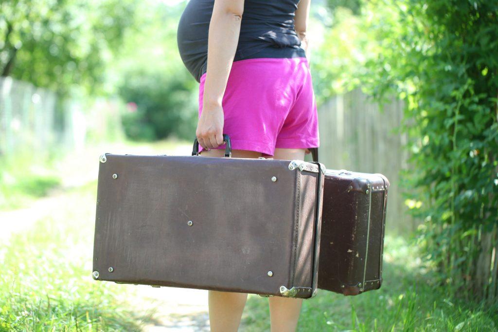 Těhotná maminka s kufry